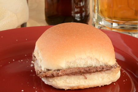 A hamburger slider with a mug of beer in the background Stock Photo