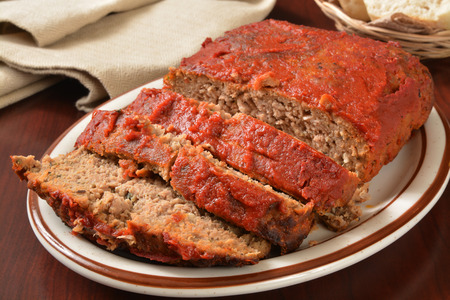 A serving platter with sliced meatloaf covered in tomato sauce
