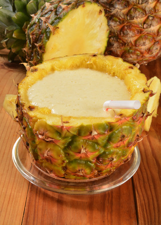 A pineapple banana smoothie in a hollowed out pineapple