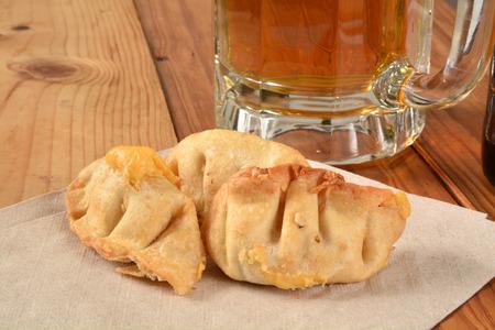 comida japonesa: Wonton fritos rellenos de crema de queso y una jarra de cerveza