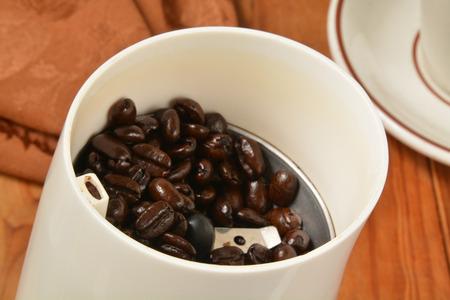 Asado francés granos de café orgánicos en un molinillo. Poca profundidad de campo, se centran en los frijoles Foto de archivo - 36123504