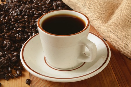 A cup of fresh brewed coffee with dark roasted coffee beans in the background