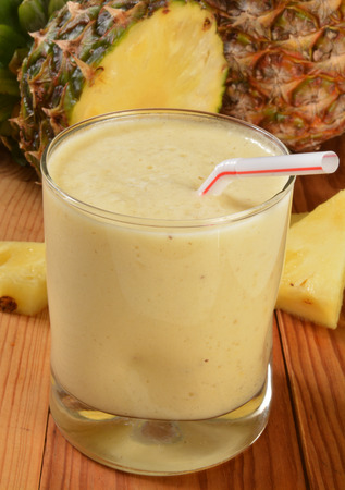 A pineapple banana smoothie on a rustic wooden table