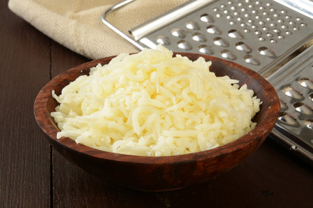 A wooden bowl of grated swiss, mozzarella, or Monterey Jack cheese Stockfoto