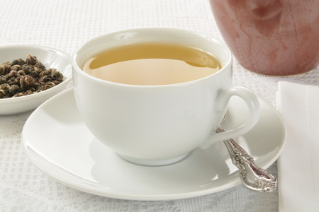 horizontal  green: A cup of green tea, with hand sewn Jasmine green tea pearls or buds in a sample dish Stock Photo