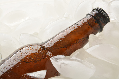 A bottle of beer chilling in a chest of ice, closeup photo
