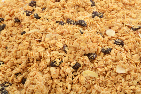 A background of honey oat granola with almonds and raisins