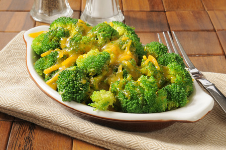 A bowl of steamed broccoli topped with cheddar cheese