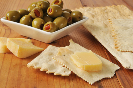 Smoked gouda cheese with flatbread crackers and green olives