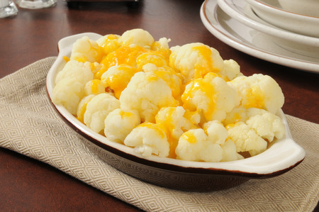 A bowl of steamed cauliflower with cheddar cheese sauce