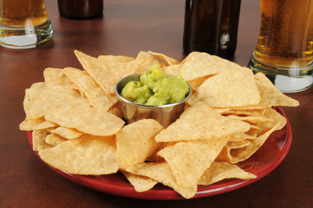 corn chips: A plate of corn chips with guacamole and beer Stock Photo