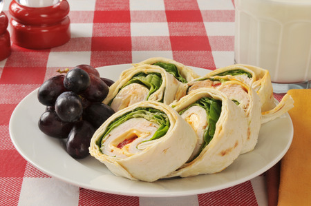 A chicken or turkey wrap sandwich wtih grapes and milk