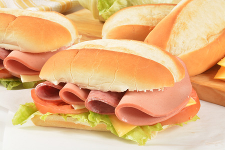 preperation: Hogie sandwiches with salami, bologna and cheeses on waxed paper Stock Photo
