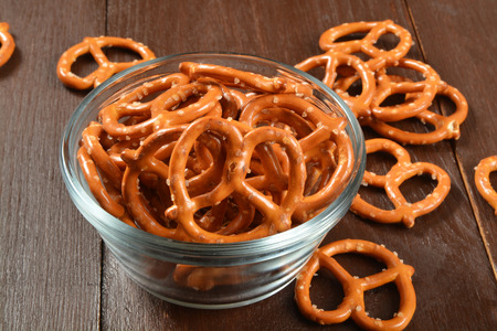 A bowl of salted pretzels on a wooden table Stock Photo