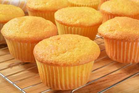 preperation: Fresh baked yellow cupcakes on a cooling rack Stock Photo