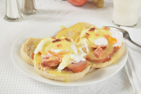 bacon bits: Eggs Benedict topped with bacon bits and a glass of milk