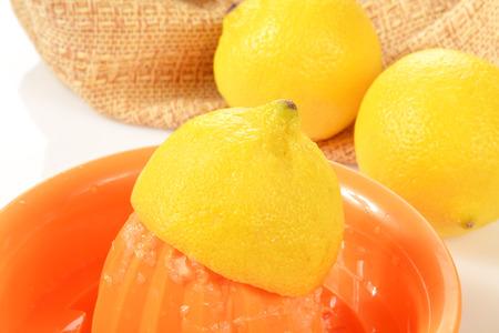 juicer: A fresh organic lemon being juiced on a juicer