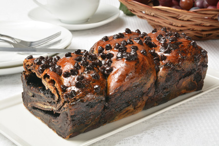 A loaf of chocolate babka with coffee in the background 스톡 콘텐츠