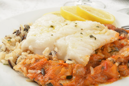 Close up of Cod Provencal on wild rice with lemon