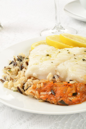 Cod Provencal on wild rice with slices of lemon Stock Photo