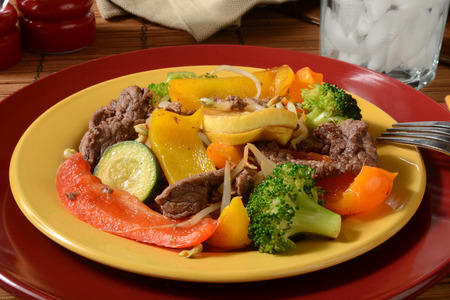 bean sprouts: A plate of beef stir fry with broccoli, zuccini, squash and bean sprouts