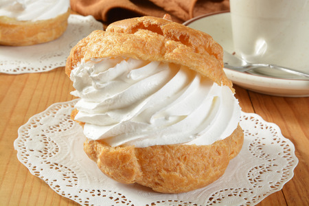 cream puff: A large golden cream puff on a doily with a cup of coffee