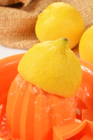 squeezed: A fresh lemon being squeezed on a juicer