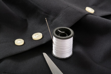 needle tip: The tip of scissors with a needle and thread by the spare button on a shirt tail