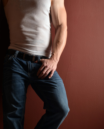 lower body: lower body shot of a muscular man in a wife beater and blue jeans Stock Photo
