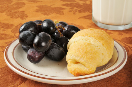 concord grape: A fresh baked croissant with a bunch of grapes and milk