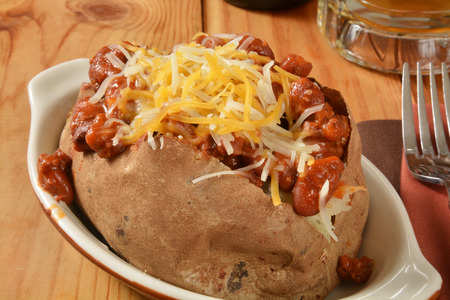 baked beans: Closeup of a baked potato with chile and cheese