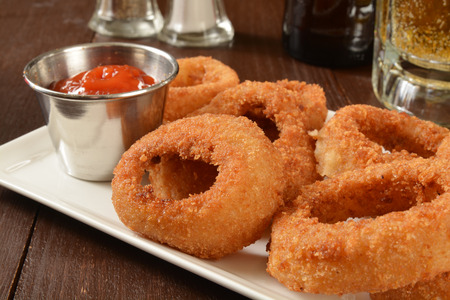 catsup: A plate of onion rings on a bar counter with a mug of beer Stock Photo