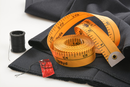 Needle and tread with a measuring tape on pants that need a hem put in