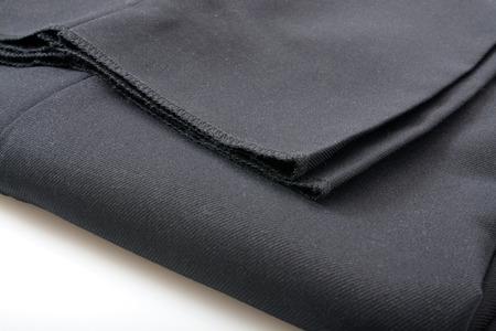 slacks: A folded pair of unhemmed mens dress slacks closeup Stock Photo