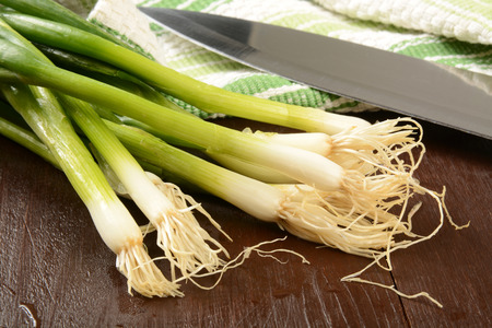 washed: Freshly washed organic green onions on a cutting board