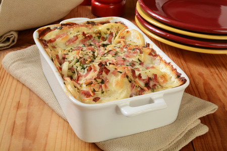 scalloped: Scalloped potatoes in cheese sauce with ham in a casserole dish Stock Photo