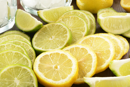 Lemon and lime slices on a counter near glasses of ice