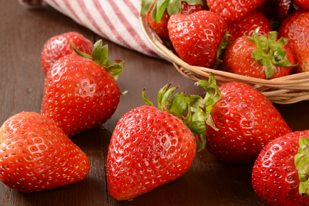 Fresh organic strawberries spilling out of a basket Stock fotó
