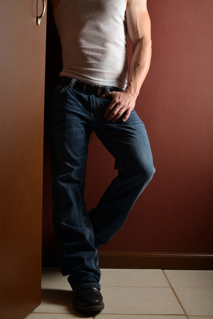 muscular man: lower body shot of a muscular man in a wife beater and blue jeans Stock Photo