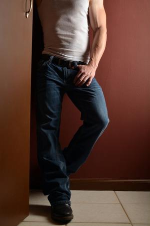 piernas hombre: menor golpe al cuerpo de un hombre musculoso con un batidor de esposa y blue jeans Foto de archivo
