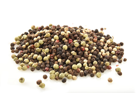 A mound of white and black peppercorns on a white counter