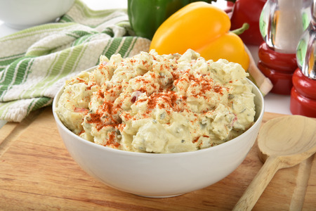 potato salad: A bowl of potato salad with peppers in the background Stock Photo