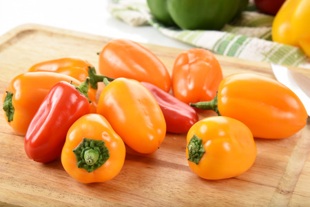 bell peppers: Mini red and yellow bell peppers on a cutting board Stock Photo