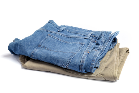 Folded blue jeans and khaki pants on a white background