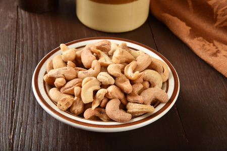 A smalll bowl of cashews on a rustic wooden table 版權商用圖片