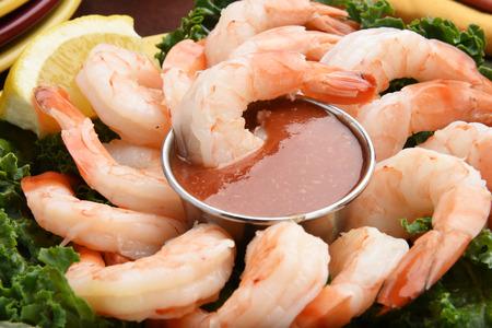 Closeup of shrimp cocktail with lemon wedges and garnish