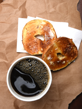 paper cup: A paper cup of coffee and a toasted buttered bagel