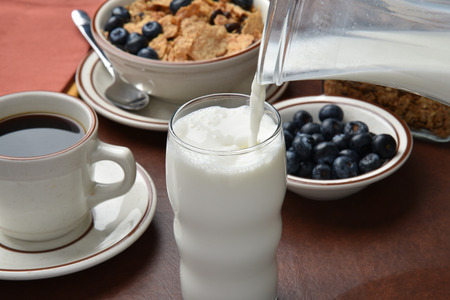Pouring milk into a glass, with cereal in the background