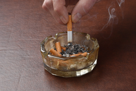 Crushing out a cigarette in a dirty ashtray