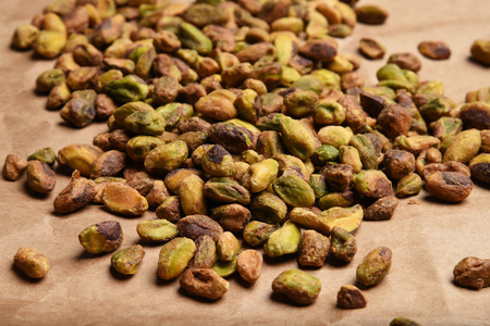 A mound of shelled pistachios on brown kraft paper
